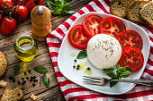 Top view of a healthy fresh burrata cheese with sliced tomatoes in a white plate placed on a gingham tablecloth shot on rustic wooden table. Ripe tomatoes, olive oil, basil, pepper and crostini complete the composition. Predominant colors are red and white. Low key DSRL studio photo taken with Canon EOS 5D Mk II and Canon EF 100mm f/2.8L Macro IS USM