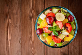 Healthy fresh fruit salad in glass bowl on wooden background. Top view.