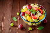 Healthy fresh fruit salad in glass bowl on wooden background. Selective focus.