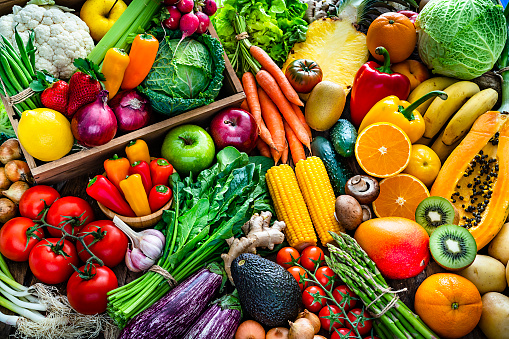 High angle view of a large assortment of healthy fresh organic fruits and vegetables. The composition includes cabbage, carrots, onion, tomatoes, raw potato, avocado, asparagus, eggplant, ginger, green beans, celery, cucumber, broccoli, lettuce, spinach, radish, lemon, apples, strawberries, pineapple, papaya, mango, banana, grape fruit, oranges, kiwi fruit among others. The composition is at the left of an horizontal frame leaving useful copy space for text and/or logo at the right. High resolution 42Mp studio digital capture taken with SONY A7rII and Zeiss Batis 40mm F2.0 CF lens