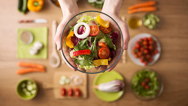 Healthy fresh homemade salad Hands holding an healthy fresh vegetarian salad in a bowl, fresh raw vegetables on background, top view healthy eating stock pictures, royalty-free photos & images