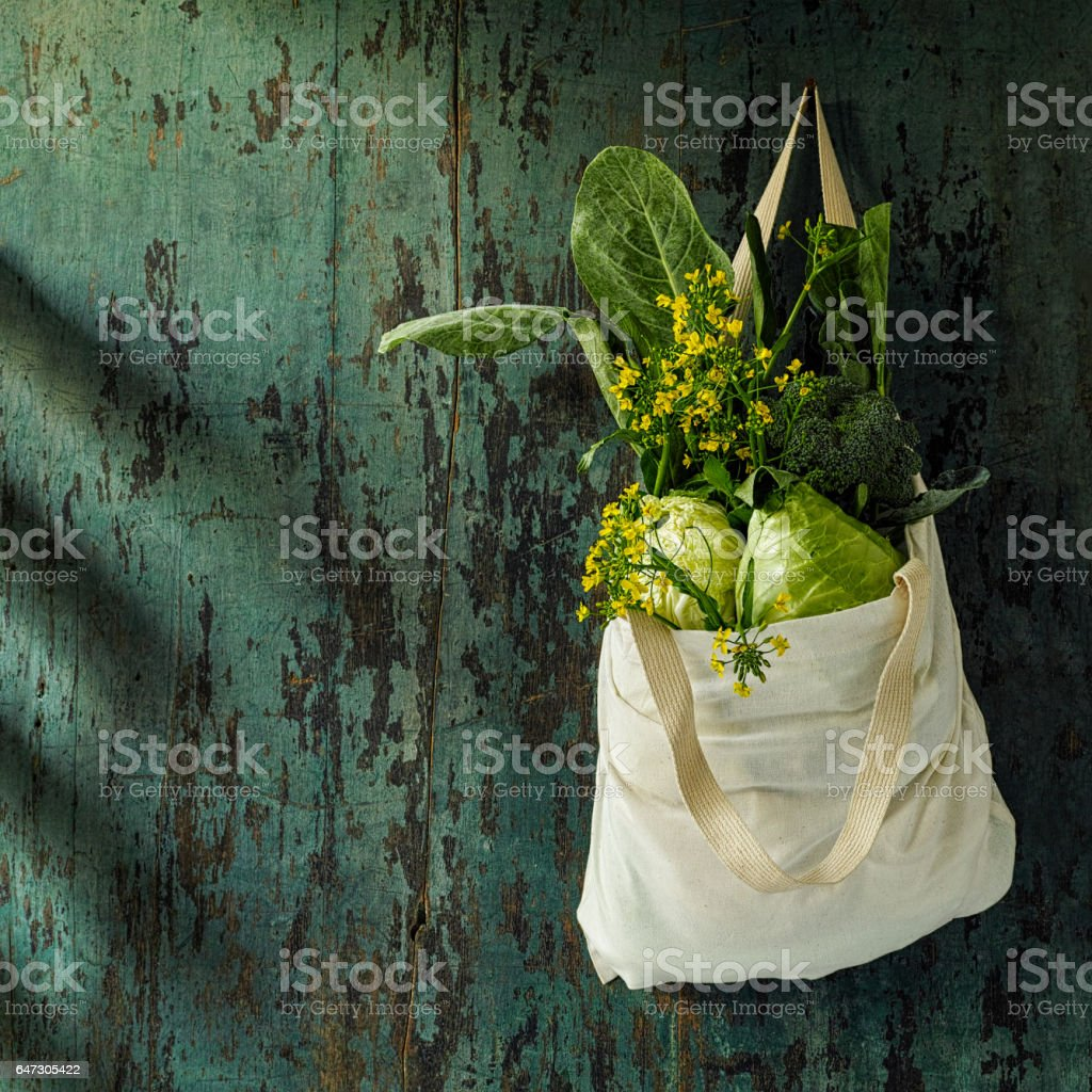 Healthy fresh leafy green vegetables hanging in a resuseable natural cotton shopping bag from a rusty nail on a worn wooden rustic board background. stock photo