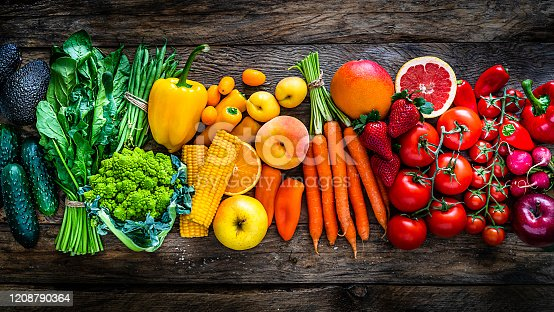 Top view of a large assortment of healthy fresh rainbow colored organic fruits and vegetables arranged side by side on rustic wooden table. The composition includes carrots, onion, tomatoes, avocado, corn, green bean, cucumber, broccoli, spinach, apples, strawberries, mango, grape fruit, peach, oranges, bell pepper, radish among others. The composition is at the left of an horizontal frame leaving useful copy space for text and/or logo at the right. High resolution 42Mp studio digital capture taken with SONY A7rII and Zeiss Batis 40mm F2.0 CF lens