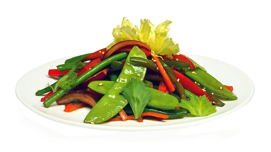 Healthy fresh salad with green beans, sweet pepper and parsley on white round plate isolated on white background. Diet conception. Close-up photo