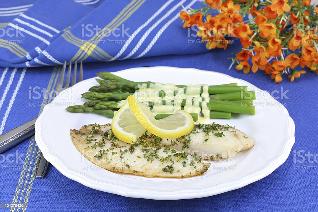 Healthy, fresh tilapia fillets with asparagus and Hollandaise sa stock photo