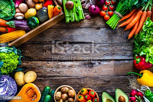 Top view of a rustic wooden table with healthy fresh organic vegetables places side by side all around the border making a frame and leaving useful copy space available for text and/or logo at the center. A wooden crate filled with vegetables is at the top left corner. The composition includes corn, edible mushrooms, cabbage, carrots, onion, squash, romanesco cauliflower, raw potatoes, tomatoes, celery, avocado, garlic, eggplant, cucumber, lettuce and radish. High resolution 42Mp studio digital capture taken with SONY A7rII and Zeiss Batis 40mm F2.0 CF lens