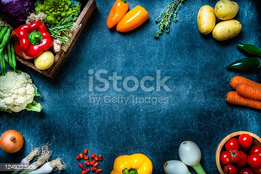 Healthy food: top view fresh multicolored organic vegetables arranged all around the border of a abstract dark blue background making a frame and leaving useful copy space for text and/or logo. Vegetables included in the composition are tomatoes, onion, carrot, green beans, bell pepper, herbs, cabbage, potatoes, among others. High resolution 42Mp studio digital capture taken with Sony A7rII and Sony FE 90mm f2.8 macro G OSS lens