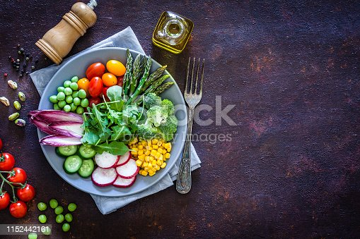 Healthy fresh vegetables salad shot from above on abstract dark brown table. The composition is at the left of an horizontal frame leaving a useful copy space for text and/or logo at the right. Vegetables included in the salad are arugula, asparagus, tomatoes, green peas, cucumber, broccoli, radish and corn. An olive oil bottle and a pepper mill complete the composition. Predominant colors are green and brown. Low key DSRL studio photo taken with Canon EOS 5D Mk II and Canon EF 100mm f/2.8L Macro IS USM.