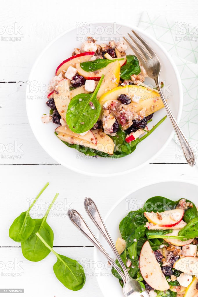 Healthy fruit and berry salad with fresh apples, cranberries, walnuts, italian ricotta cheese and spinach leaves. Delicious and nutritious diet dish for breakfast. Salad bowls on white wooden background. Overhead view - Royalty-free Antioxidant Stock Photo