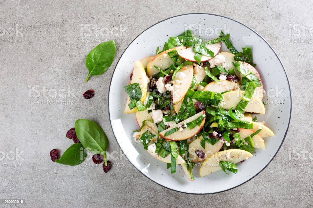 Healthy fruit and berry salad with fresh apples, cranberries, walnuts, italian ricotta cheese and spinach leaves. Delicious and nutritious diet dish for breakfast. Salad bowls on grey stone background. Top view stock photo