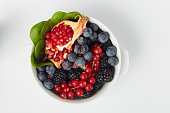 Raw fruits and vegetables like; Blueberry, blackberry, spinach, pomegranate, cranberry in a white bowl over white surface.