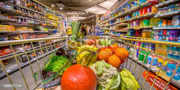 Healthy Fruit and vegetables in Grocery shop cart in supermarket filled with food products as seen from the customers point of view