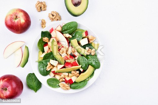 Fruit salad with red apples, avocado, spinach and walnut on light background with copy space, top view