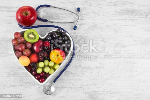 Heart health, and cholesterol diet concept. Healthy fruits in heart shaped bowl with stethoscope and green apple on white vintage wooden table.