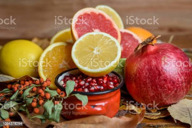 Photo of Healthy fruits - lemons, oranges, pomegranate, grapefruit, pomegranate seed, slides, autumn leaf