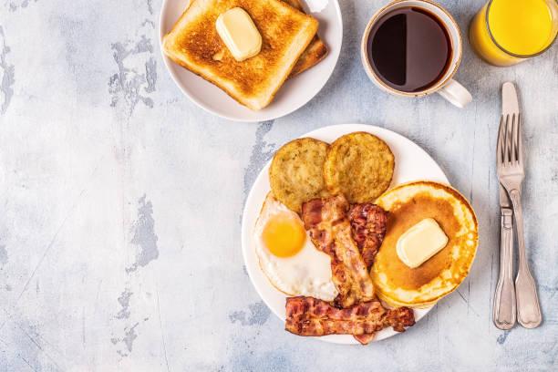 saludable desayuno americano con huevos bacon tortitas y latkes - desayuno fotografías e imágenes de stock