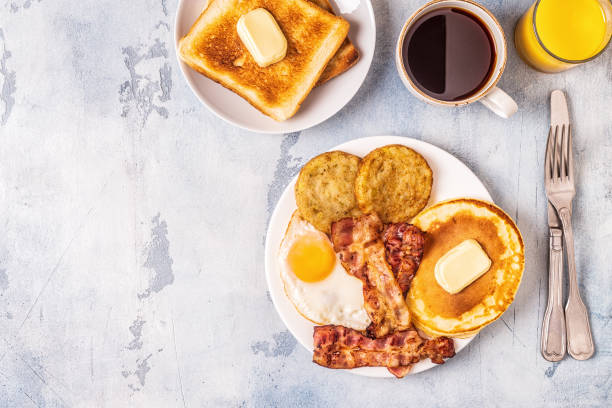 Healthy Full American Breakfast with Eggs Bacon Pancakes and Latkes Healthy Full American Breakfast with Eggs Bacon Pancakes and Latkes, top view. breakfast stock pictures, royalty-free photos & images