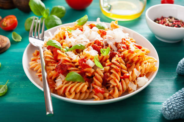 healthy fusilli pasta with tomato sauce parmesan basil healthy fusilli pasta with tomato sauce parmesan basil fusilli stock pictures, royalty-free photos & images