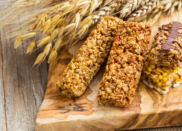 Healthy granola cereal bars with wheat ears on wooden board stock photo