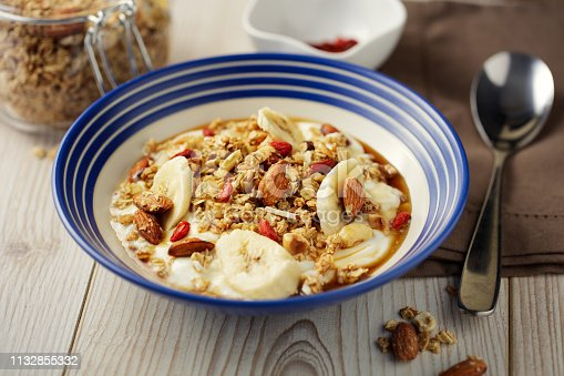 Home made freshness home made granola with nature yogurt sliced banana and maple syrup
