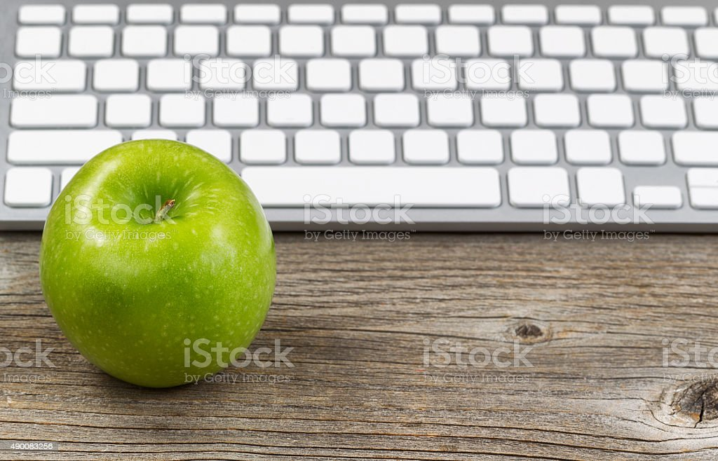 Healthy green apple with keyboard on rustic wooden desktop stock photo