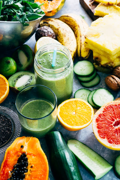 Healthy green detox  smoothie drink Healthy mango and green detox  smoothie drink in a glass surrounded by raw fruit ingredients,banana,ananas, papaya,cucumber, kale,spinach, anti inflammatory stock pictures, royalty-free photos & images