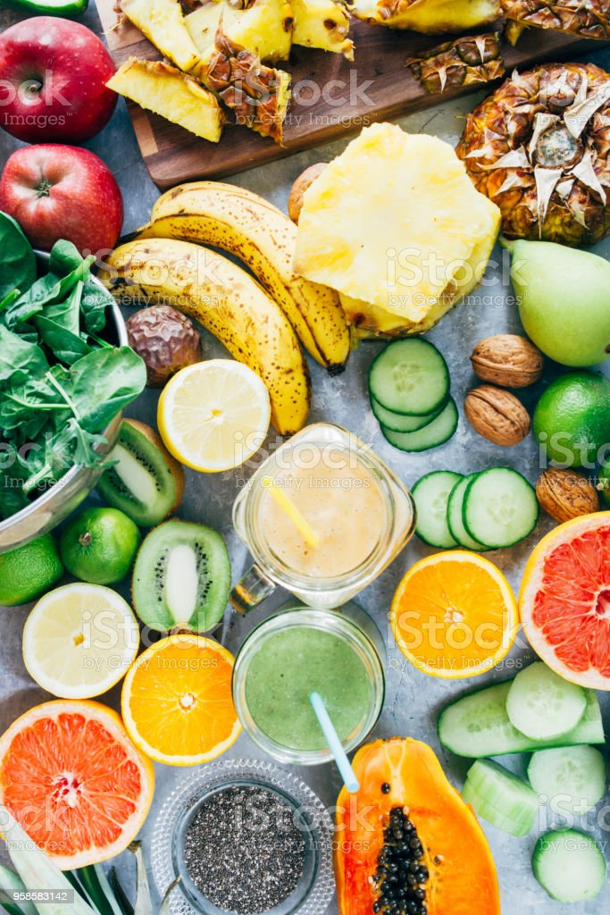 Healthy green detox  smoothie drink Healthy mango and green detox  smoothie drink in a glass surrounded by raw fruit ingredients,banana,ananas, papaya,cucumber, kale,spinach, Anti-inflammatory Stock Photo
