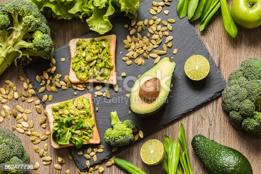 istock Healthy green food. Vegan sandwiches with avocado and vegetables on wooden background. 862477796