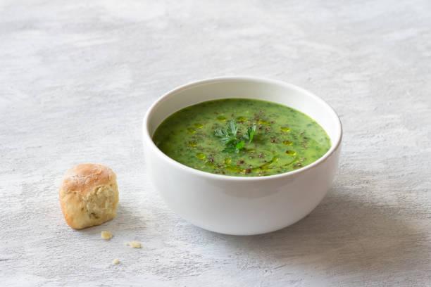 Gesunde grün grüne Grünkohlcremesuppe mit Kartoffeln und Brot auf grauem Hintergrund – Foto