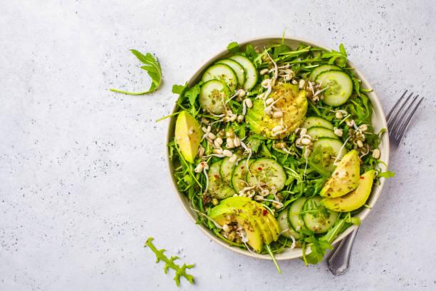 gezonde groene salade met avocado, komkommer en rucola in witte schotel, bovenaanzicht, kopieer ruimte. - salade stockfoto's en -beelden