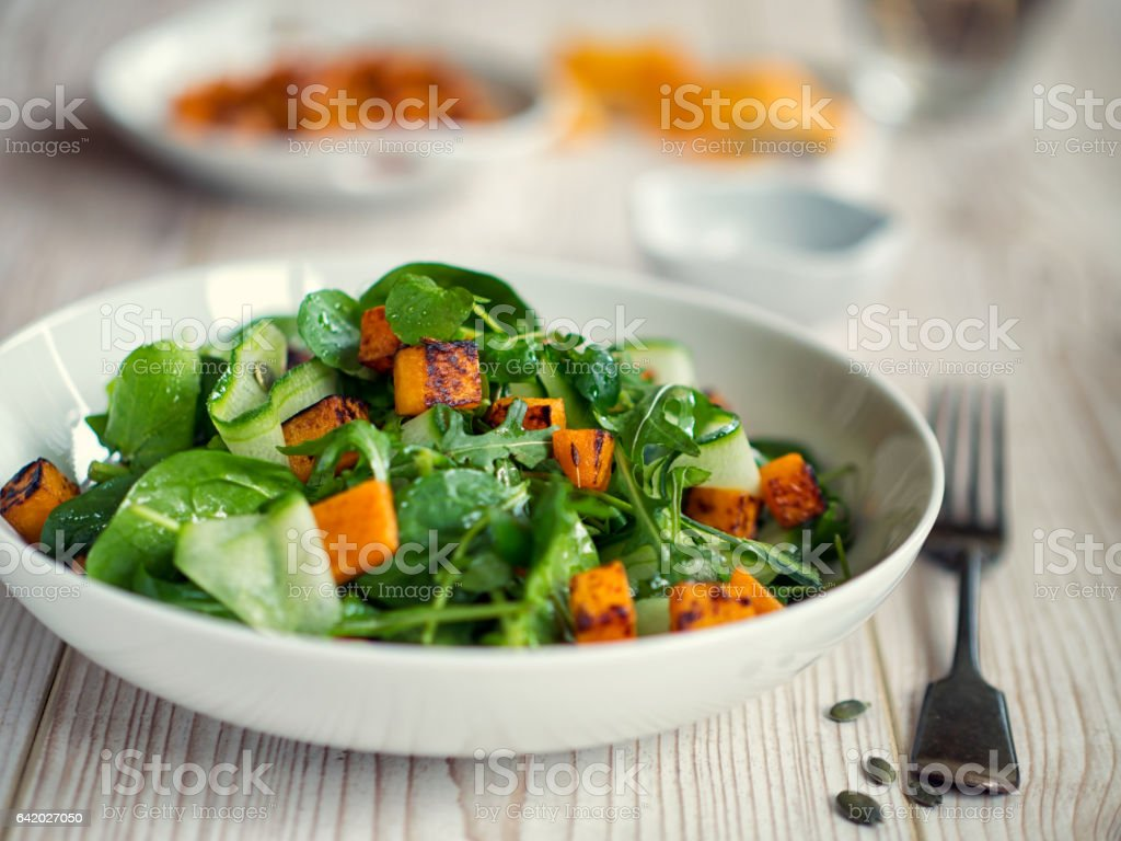 Healthy green salad with roasted butternuts squash stock photo