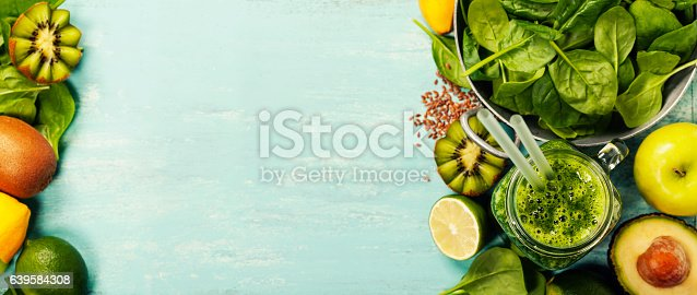 istock Healthy green smoothie and ingredients on blue background 639584308