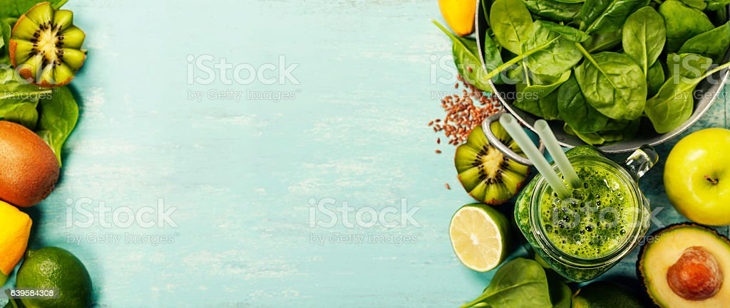 Healthy green smoothie and ingredients on blue background stock photo