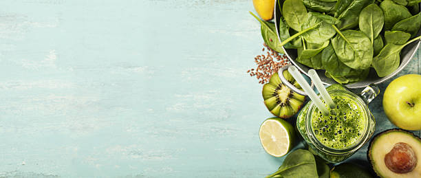 Healthy green smoothie and ingredients on blue background