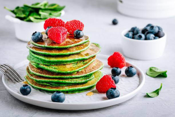 Healthy green spinach pancakes with raspberries, blueberries and honey stock photo