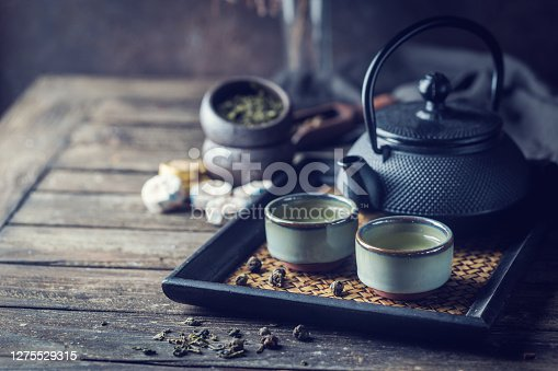 Still-life of japanese healthy green tea in a small cups and teapot over dark background