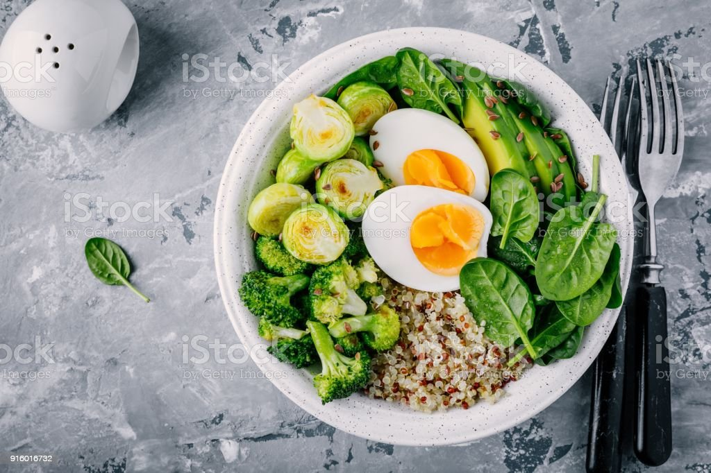 Healthy green vegetarian buddha bowl lunch with eggs, quinoa, spinach, avocado, grilled brussels sprouts and broccoli on dark gray background. stock photo
