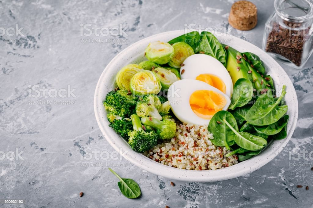 Healthy green vegetarian buddha bowl lunch with eggs, quinoa, spinach, avocado, grilled brussels sprouts and broccoli with flax seeds stock photo