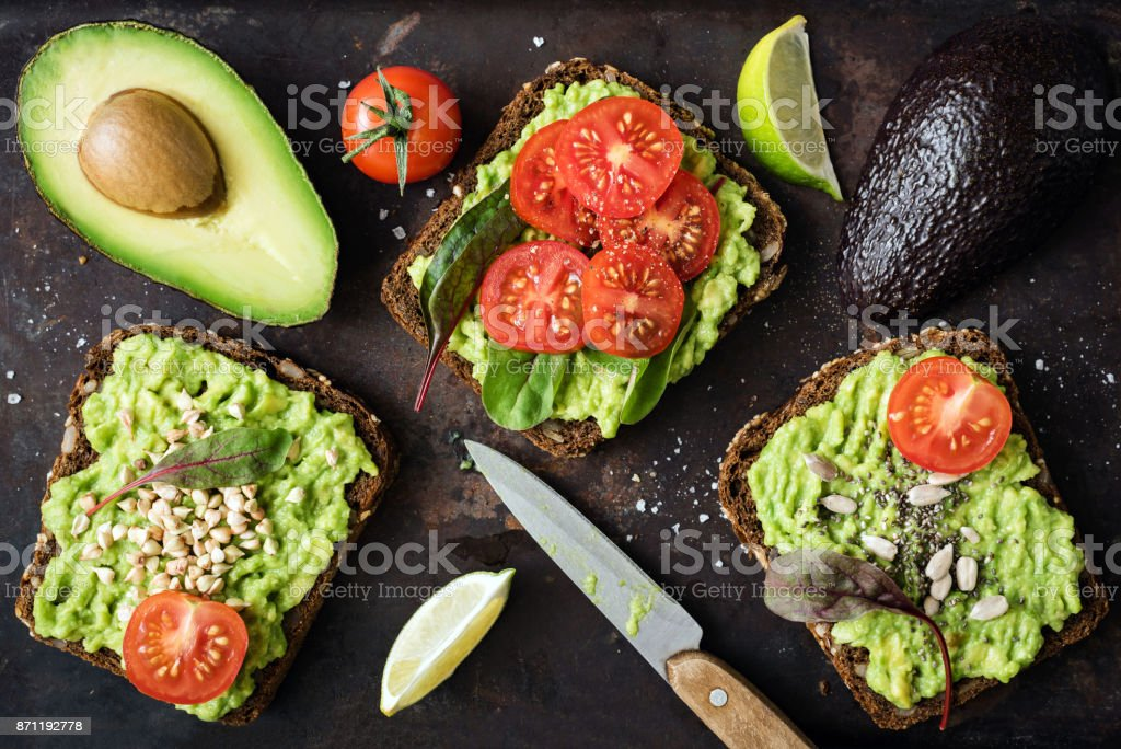 Healthy green veggie avocado toast with sprouts stock photo