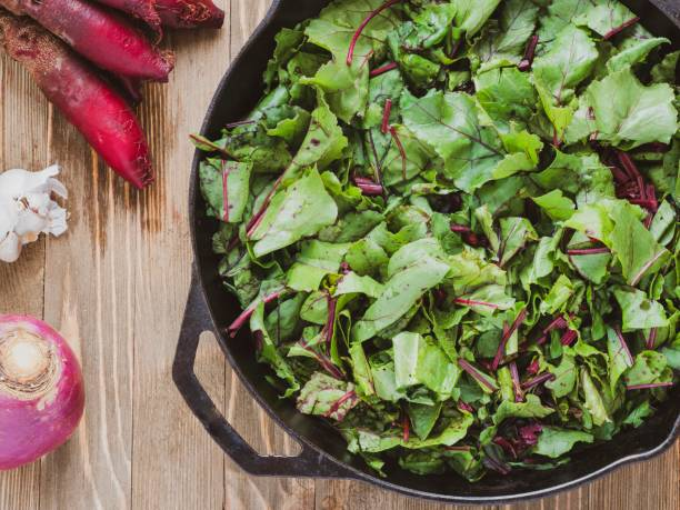 Healthy greens Beet greens in a cast iron skillet ready for cooking. brassica rapa stock pictures, royalty-free photos & images