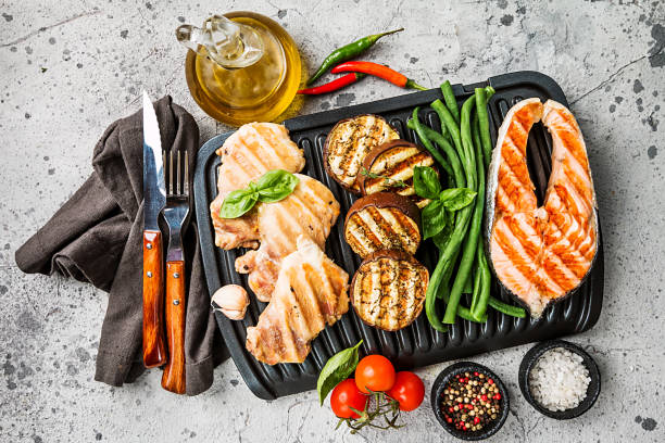 Healthy grill food healthy food - grilled salmon steak, chicken and vegetables over gray background, top view leaning stock pictures, royalty-free photos & images