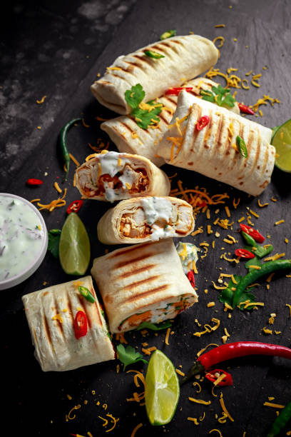 healthy grilled chicken and parsley wraps, loaded with cheese, served with greek yogurt deep, chillies and lime slices - xaile imagens e fotografias de stock