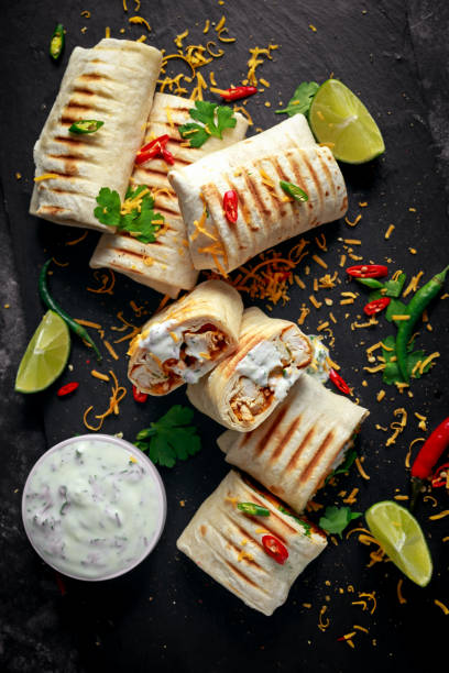 healthy grilled chicken and parsley wraps, loaded with cheese, served with greek yogurt deep, chillies and lime slices - avvolgere foto e immagini stock