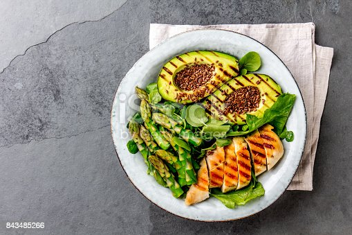 istock Healthy grilled chicken, grilled avocado and asparagus salad with linen seeds. Balanced lunch in bowl. Gray slate background. Top view 843485266
