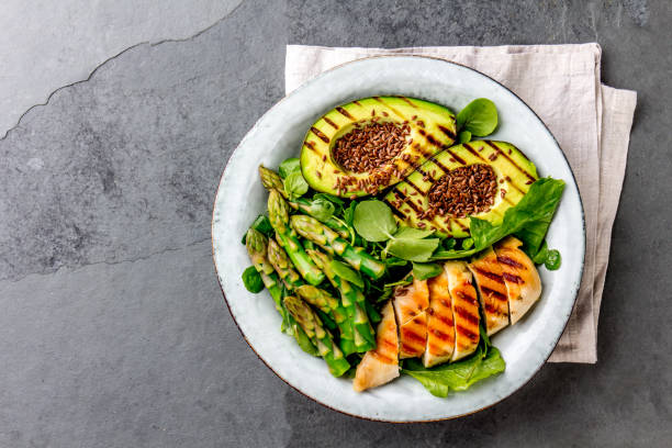 Healthy grilled chicken, grilled avocado and asparagus salad with linen seeds. Balanced lunch in bowl. Gray slate background. Top view stock photo