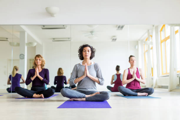 Healthy group of females meditating in yoga pose in gym Indoor shot of healthy group of females meditating in yoga pose in gym. Women practising lotus pose in fitness centre. yoga studio stock pictures, royalty-free photos & images