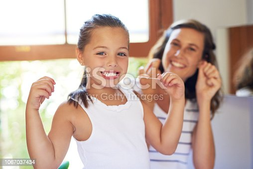 Portrait of an adorable little girl flossing her teeth with her mother at home
