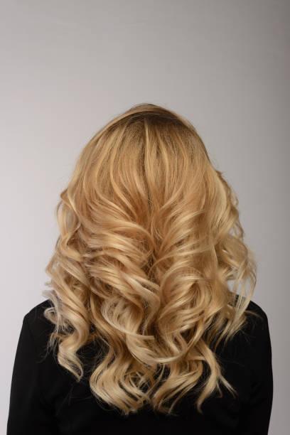 gesundes haar. lockige lange frisur. rückansicht des blonden haare. - haare ohne lockenstab wellen stock-fotos und bilder