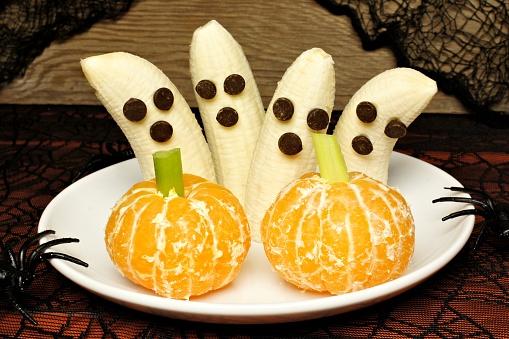 istock Healthy Halloween banana ghosts and orange pumpkins 487479412