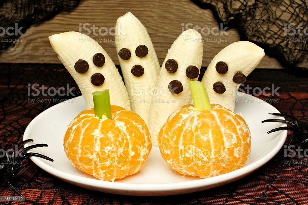 Healthy Halloween banana ghosts and orange pumpkins stock photo